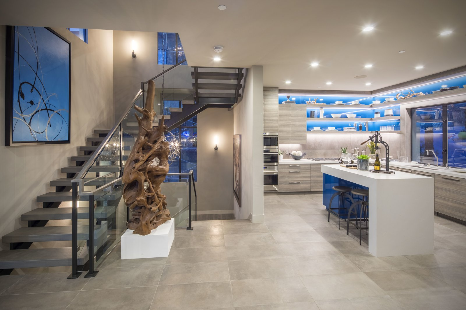 Kitchen, Recessed Lighting, Quartzite Counter, Cooktops, Laminate Cabinet, Wall Oven, Ceramic Tile Floor, Microwave, and Drop In Sink The second level kitchen is tucked behind the floating stairs while remaining open to the great room.  Vu at MacDonald Highlands by KTGY Architecture + Planning