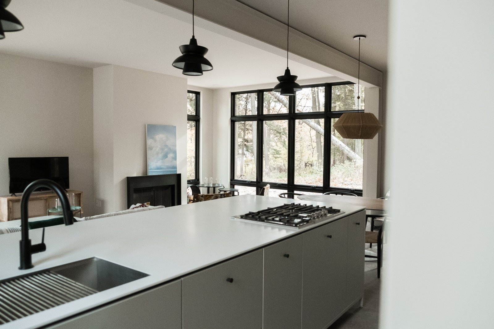Kitchen, Engineered Quartz Counter, Concrete Floor, Range, Dishwasher, Undermount Sink, and Pendant Lighting View from kitchen island to great room with steel mantel fireplace and floor-to-ceiling windows.  North Shore #7 by Hygge Supply