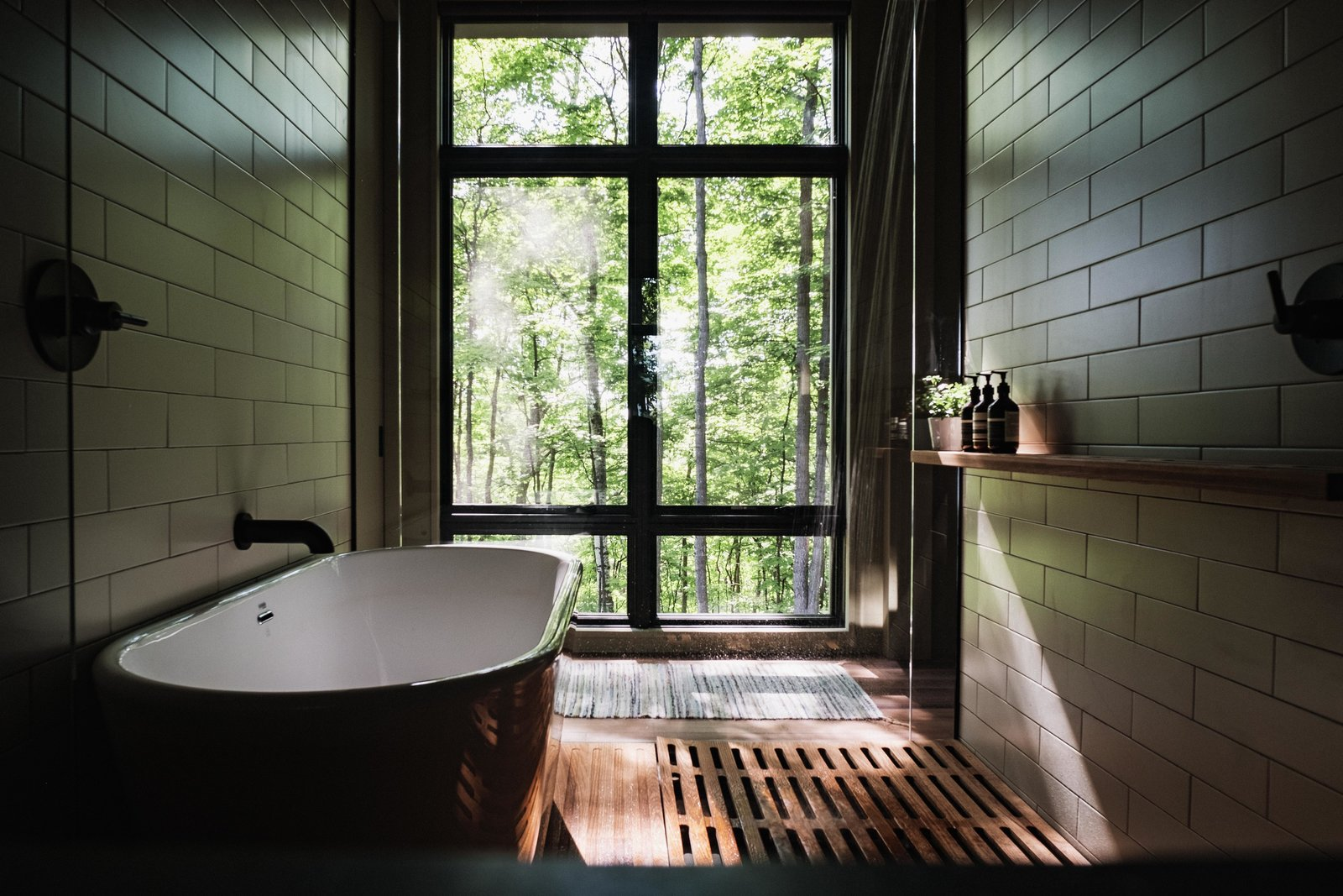 Bath, Pendant, Undermount, Soaking, Medium Hardwood, Two Piece, Open, Ceiling, Freestanding, and Subway Tile Master bath wet room with views of trees.  Best Bath Two Piece Pendant Open Freestanding Subway Tile Photos from Birch Le Collaboration House