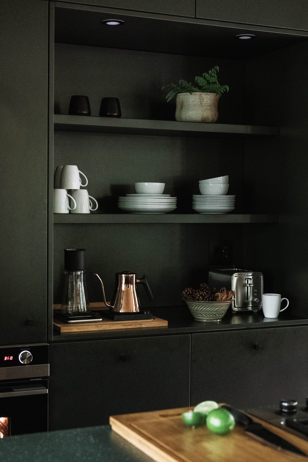 Kitchen, Undermount Sink, Refrigerator, Ceiling Lighting, Cooktops, Medium Hardwood Floor, Colorful Cabinet, and Wall Oven Hygge Supply cabinets with shelving inserts in kitchen.  Best Photos from Birch Le Collaboration House