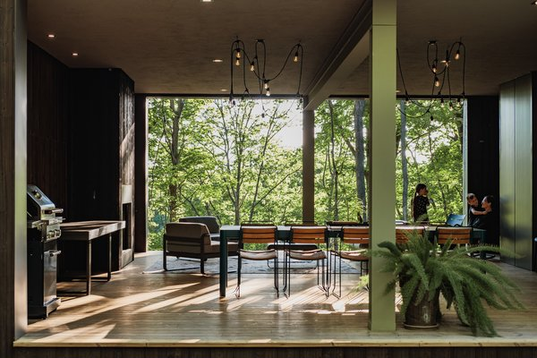 The outdoor living space of the Birch Le Collaboration House features a wood-burning fireplace under large, covered porch.
