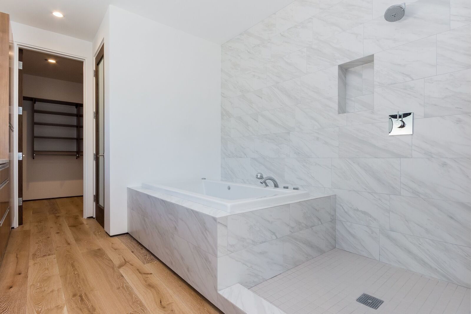 Bath Room, Medium Hardwood Floor, Quartzite Counter, Undermount Sink, Drop In Tub, Whirlpool Tub, Full Shower, Enclosed Shower, Ceiling Lighting, Porcelain Tile Wall, and One Piece Toilet Master Bath with dual shower heads including rain head / jet tub  Mammoth Modern House 1