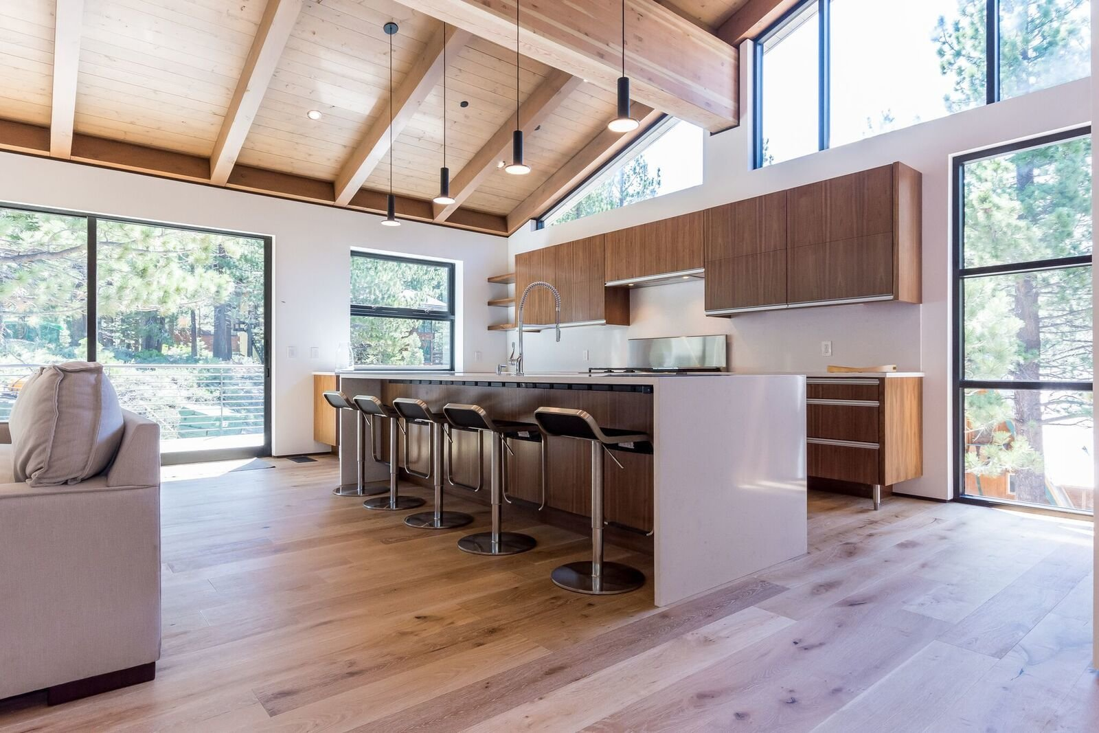 Kitchen, Engineered Quartz Counter, Quartzite Counter, Wood Cabinet, Medium Hardwood Floor, Ceiling Lighting, Pendant Lighting, Range, and Undermount Sink Seating for 5 at the large island counter  Mammoth Modern House 1