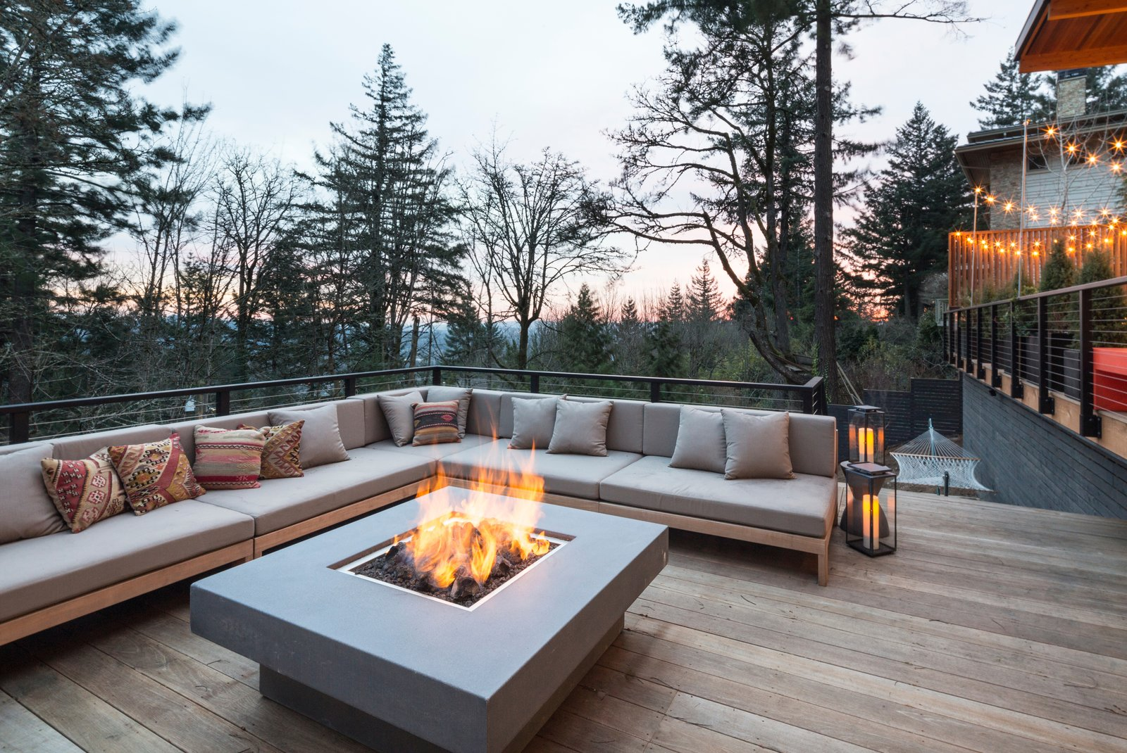 Outdoor, Hardscapes, Horizontal Fences, Wall, Wood Patio, Porch, Deck, Raised Planters, Large Patio, Porch, Deck, Trees, Decking Patio, Porch, Deck, Metal Fences, Wall, Hanging Lighting, Wood Fences, Wall, Back Yard, Landscape Lighting, and Wire Fences, Wall Fire pit terrace  The Greenhills House