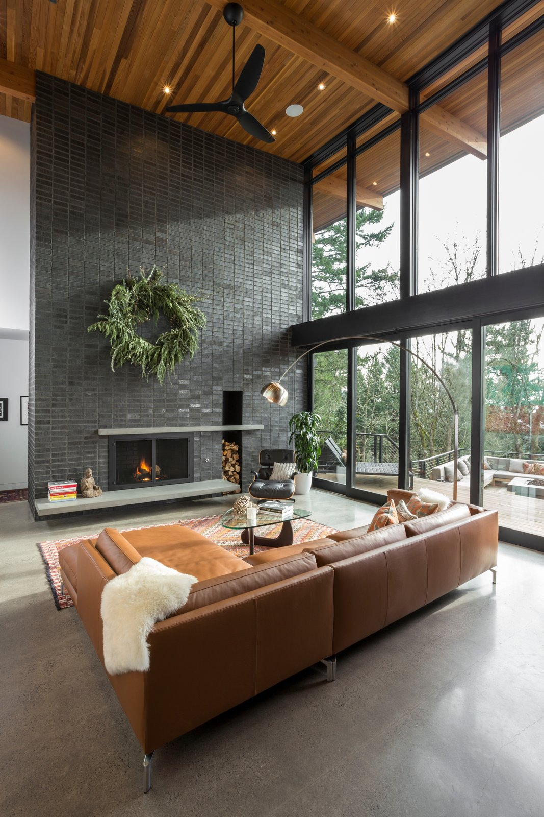 Living Room, Accent Lighting, Concrete Floor, Standard Layout Fireplace, Ceiling Lighting, Sectional, Chair, Floor Lighting, Recessed Lighting, Wood Burning Fireplace, and Coffee Tables Living room  The Greenhills House