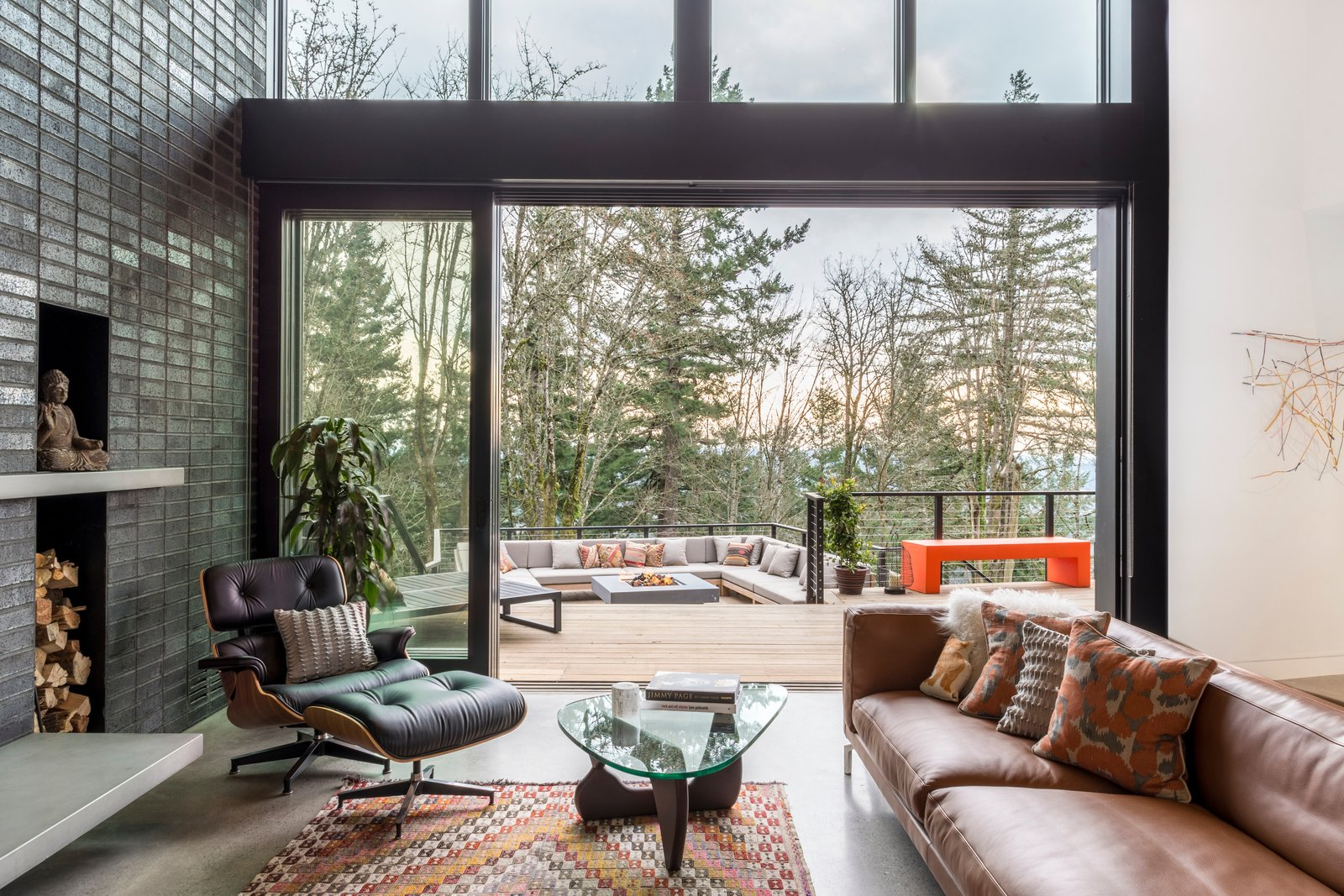 Living Room, Concrete Floor, Ceiling Lighting, Sectional, Coffee Tables, Recessed Lighting, Chair, Accent Lighting, Wood Burning Fireplace, and Standard Layout Fireplace Indoor-outdoor living rooms  The Greenhills House