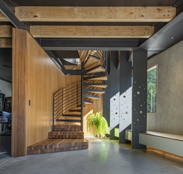 The timber-clad stairwell uses the stack effect to draw cool air from the concrete slab and masonry walls through the upper levels of the house.