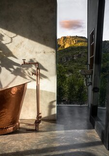 A bespoke copper bathtub and matching tapware is framed by expansive mountainside views.