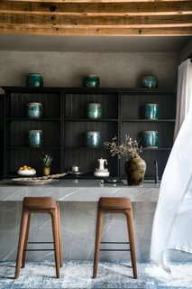The kitchen features exposed wooden beams, textured concrete walls, porcelain countertops, blackened walnut cabinets, walnut bar stools, and antique jade vases.