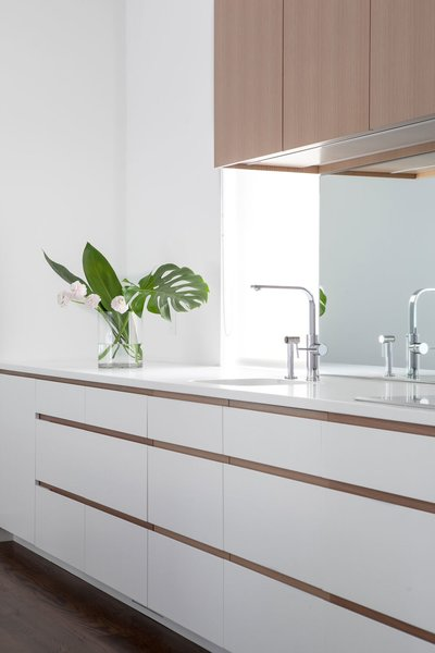 Mirrored backsplash deflects light from the opposite window and softens a typically, hard, utilitarian surface.