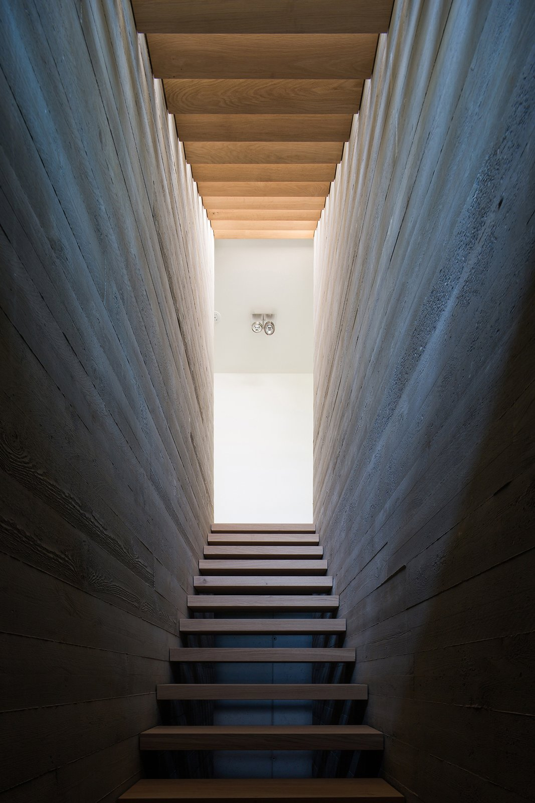 Staircase and Wood Tread Villa H | oak wooden stairs between raw concrete walls  Photos from Villa H by BERG + KLEIN