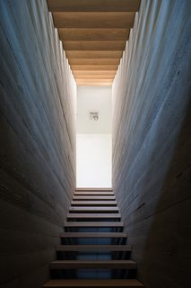 Villa H | oak wooden stairs between raw concrete walls