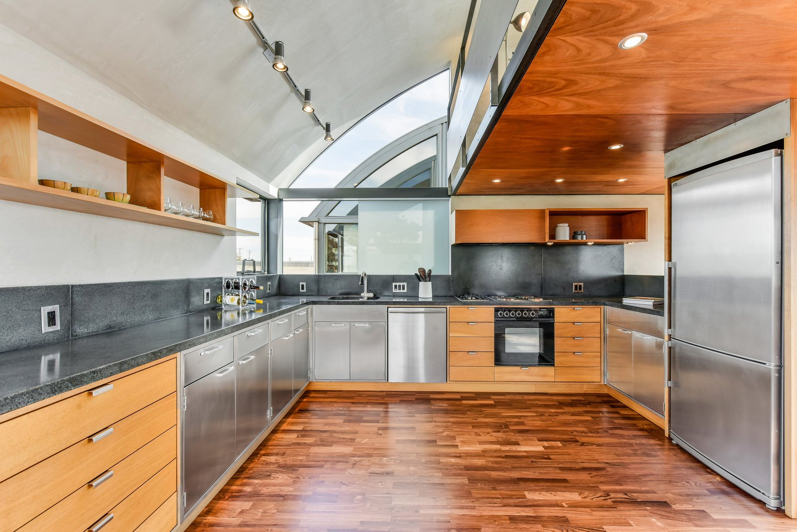 Kitchen, Medium Hardwood, Concrete, Wood, Concrete, Track, Ceiling, Refrigerator, Wall Oven, Range, Range Hood, Cooktops, Dishwasher, and Drop In Level 3 kitchen  Best Kitchen Concrete Cooktops Ceiling Range Wood Photos from The Rempel Temple