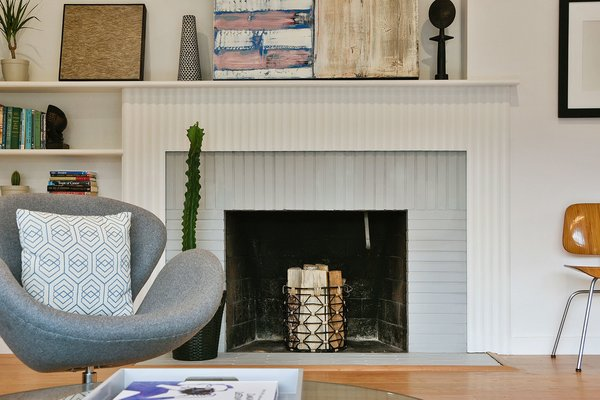 This midcentury modern home that dates from 1952 was given a fresh renovation before it was put back on the market. The happy, modern home gives a nod to its original construction with details like a fireplace with painted grey bricks and white mantel.