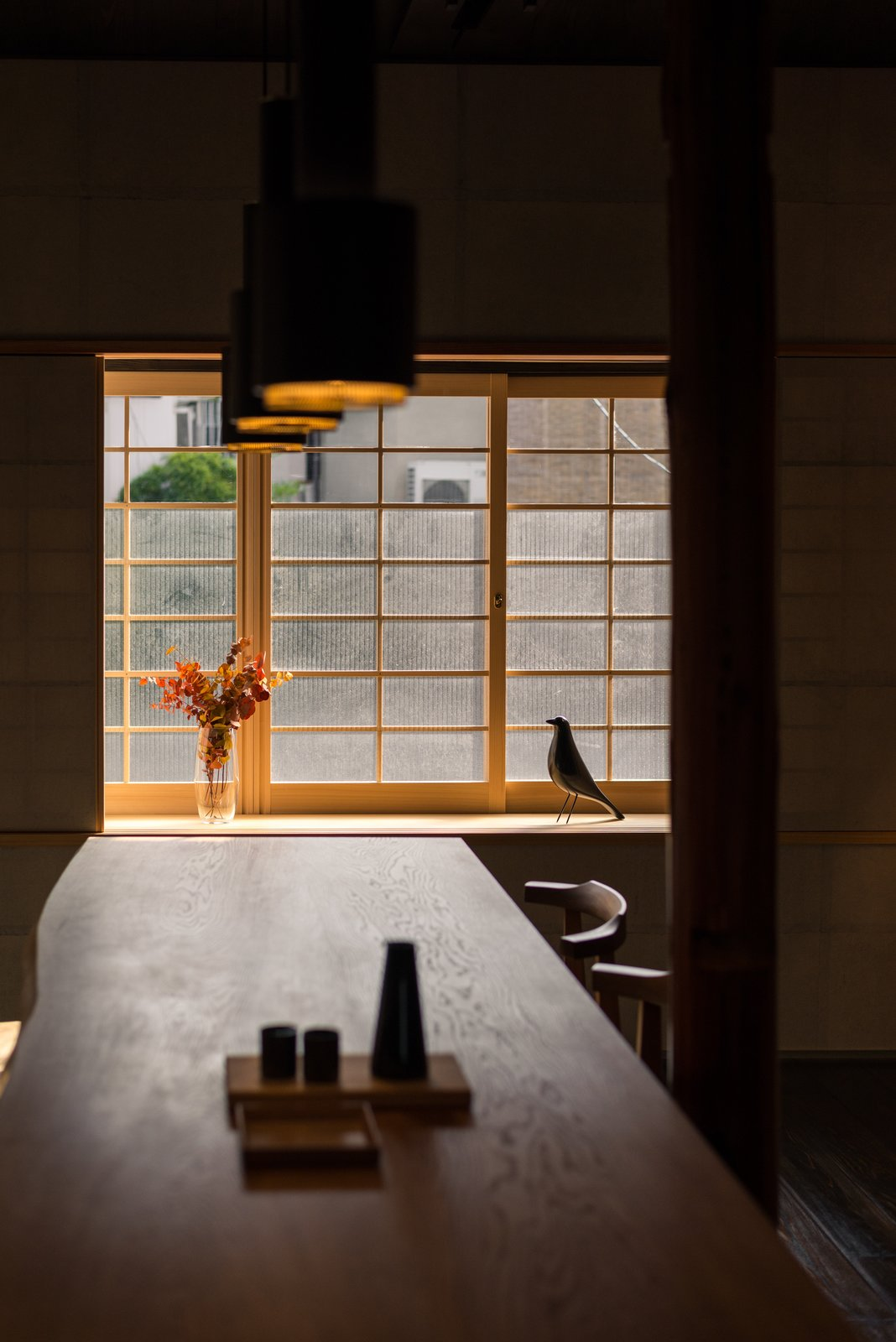 Dining Room, Table, Painted Wood Floor, Chair, and Pendant Lighting A fixed oak dining table is supported from the building structure, allowing it to almost float in space.  Ichijoji House by atelier Luke