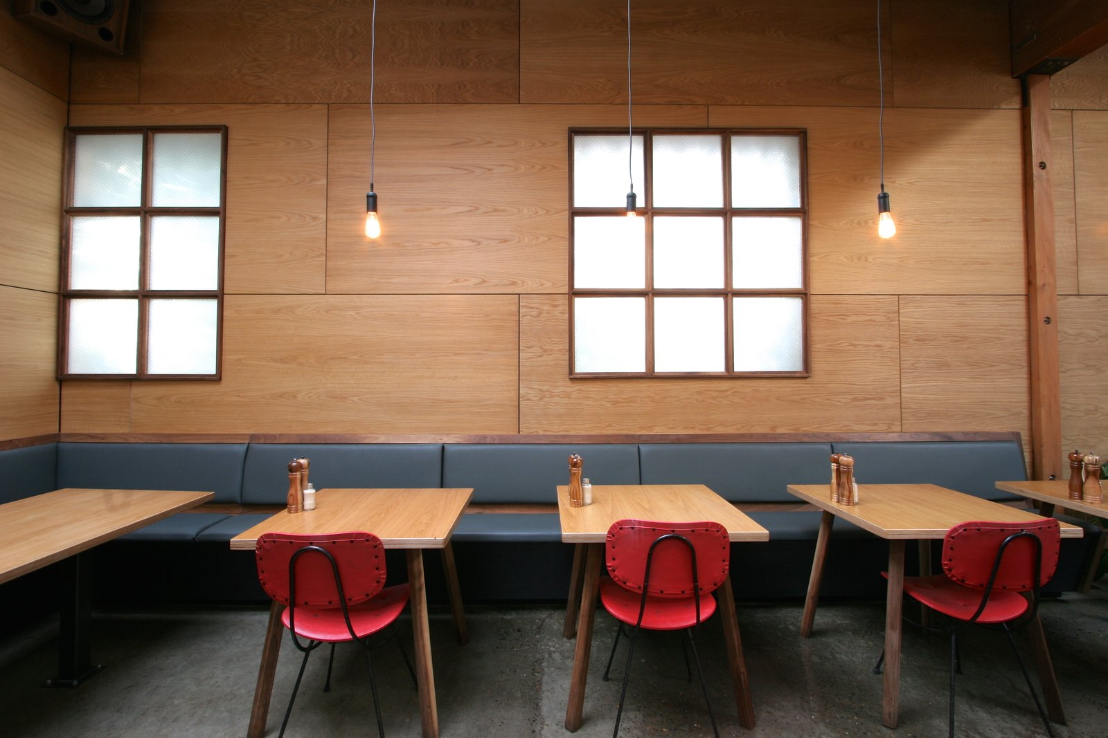 Dining Room, Bench, Chair, Table, Pendant Lighting, and Concrete Floor Red chairs lend a pop of color against rich oak walls, and walnut and leather banquets.  Photo 4 of 8 in An Australian Cafe Filled With Handcrafted Details Comes to Portland, Oregon