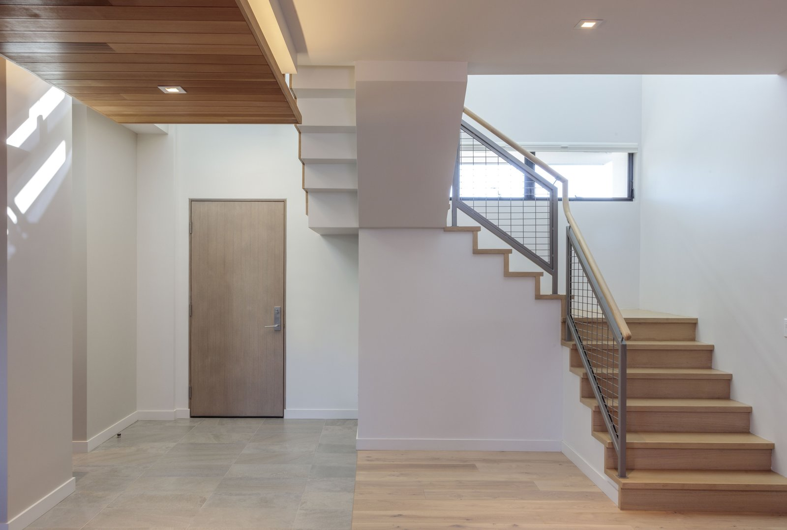 Staircase, Wood Tread, Metal Railing, and Wood Railing entry and stair  Legal House