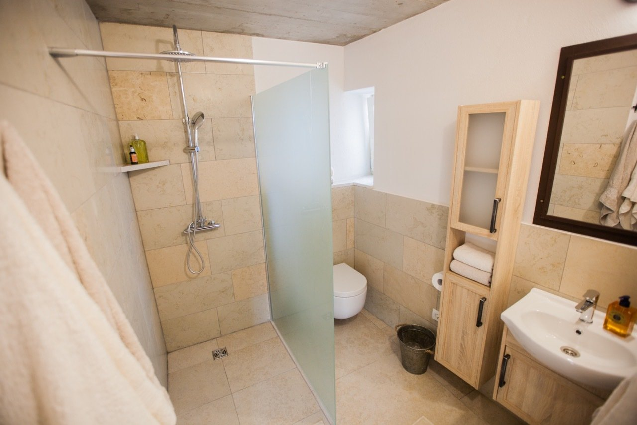 Bath Room, Limestone Floor, Drop In Sink, Open Shower, Wall Lighting, Stone Tile Wall, One Piece Toilet, and Stone Counter Bathroom 1  Villa No24