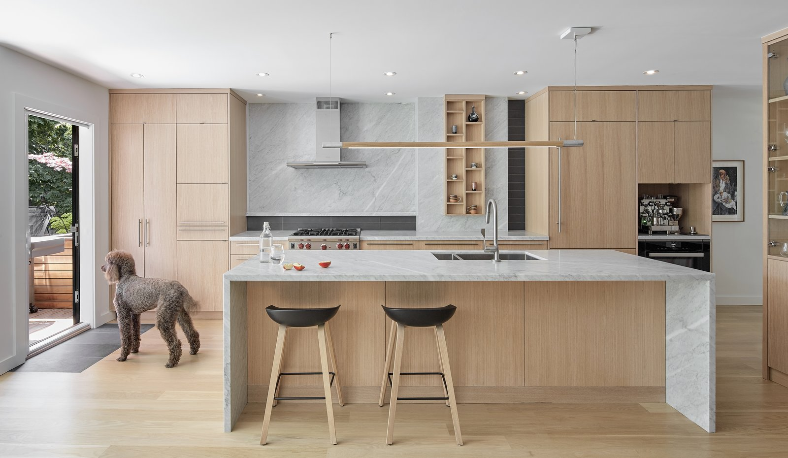 Kitchen, Light Hardwood Floor, Wood Cabinet, Range, Refrigerator, Wood Counter, Undermount Sink, Beverage Center, Stone Slab Backsplashe, Marble Counter, and Pendant Lighting Kitchen  North Toronto Addition by Asquith Architecture