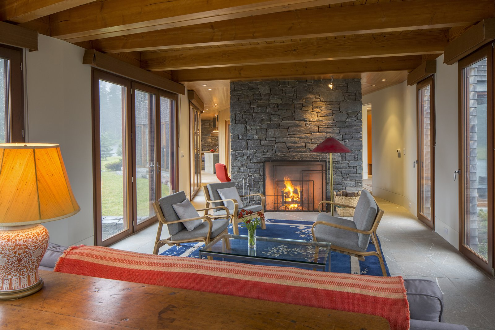 Living Room, Coffee Tables, Sofa, Chair, Lamps, Ceiling Lighting, Floor Lighting, Table Lighting, Table, Limestone Floor, and Wood Burning Fireplace Living room from the south  Deep Cove House by Elliott + Elliott Architecture