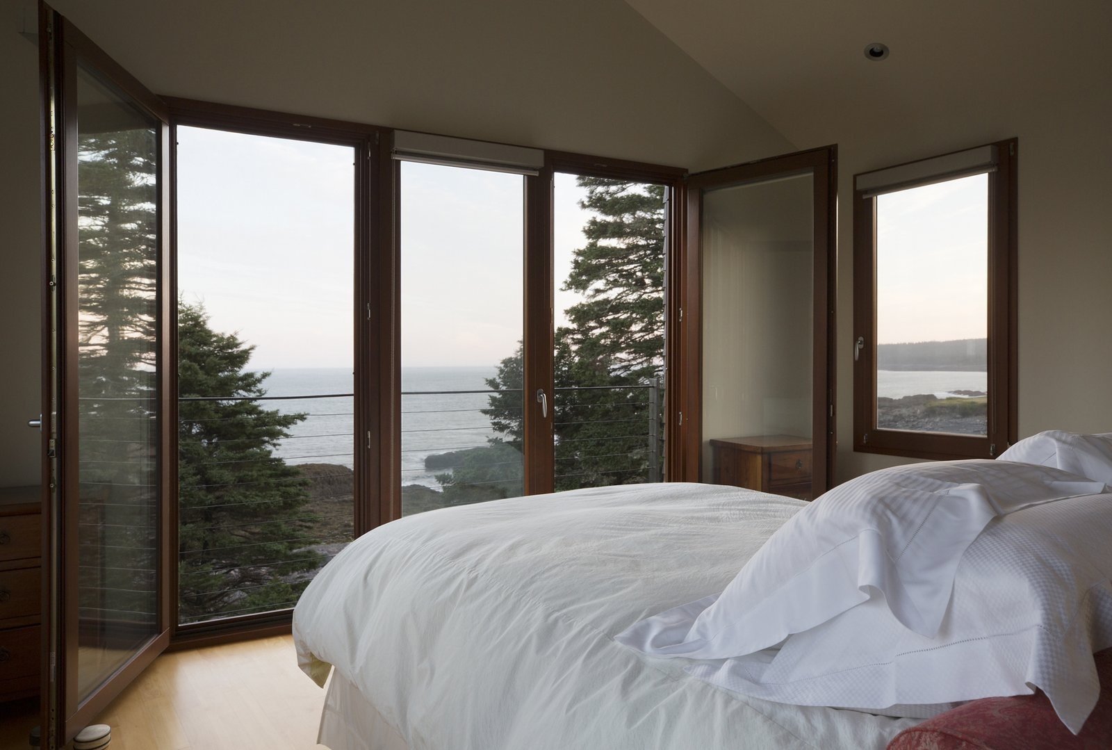 Bedroom, Bed, Dresser, Ceiling Lighting, Table Lighting, and Light Hardwood Floor View from the owner's bedroom  Deep Cove House by Elliott + Elliott Architecture