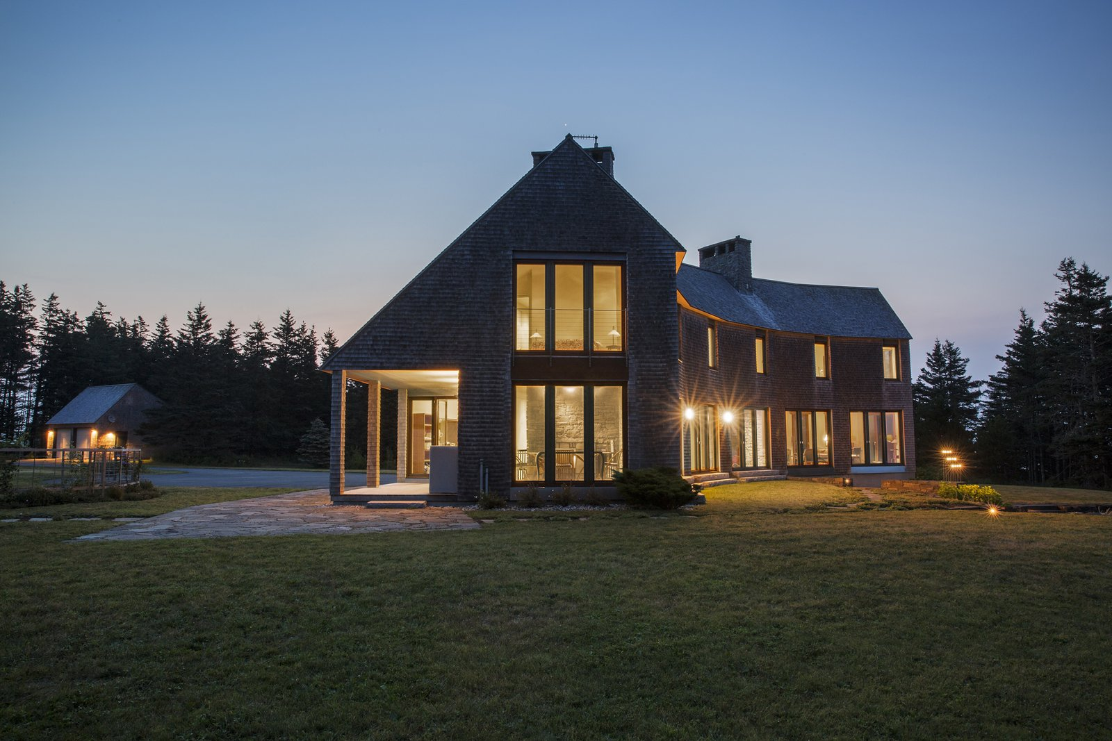 Exterior, Shingles Roof Material, House Building Type, Wood Siding Material, and Gable RoofLine West facade (dining room, guest bedroom) at night  Deep Cove House by Elliott + Elliott Architecture