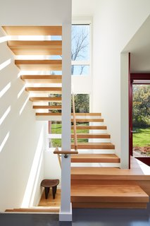 A modern staircase creates a visual connection to the woodland that surrounds the property.