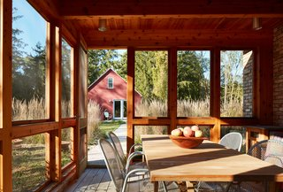 Off of the kitchen, the screened porch helps transition from the indoors to the outdoors, with the artist studio nearby.