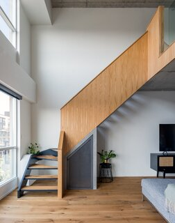 The structure of the stair was maintained, but the treads were replaced with new engineered wood flooring that got a coat of black paint.