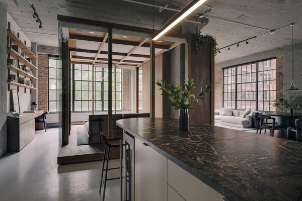 A linear suspension light from the Mile Collection by Lambert & Fils hangs above the nine-foot-long black granite island.