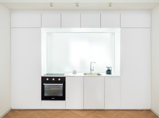 A two-way carpentry wall made from a sheet of tempered glass – 113 CM high and 208 CM wide – the wall divides the kitchen and the bathroom space, while letting light from the bathroom window infiltrate into the cooking area