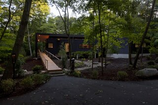 Front approach reveals entry bridge and house in the woods.