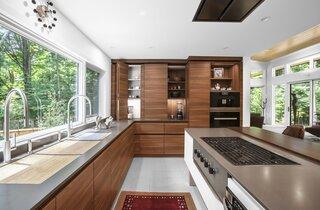 Modern kitchen includes triple-bay sink, gas range, and hidden storage.