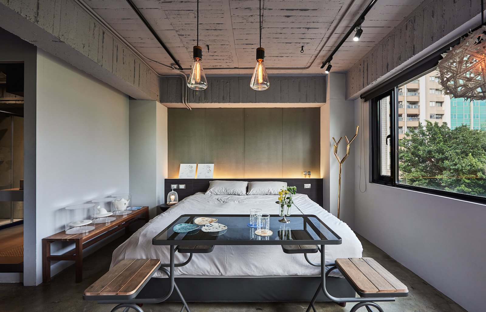 Bedroom, Pendant, Bed, Bench, Track, Concrete, Night Stands, and Accent Located on the fifth floor of an unassuming building in Datong district, Play Design Hotel is a hidden gem with only a small sign to announce its presence. Polished concrete walls and floors coupled with large, black, metal-framed windows create an elegant backdrop for the hand-picked design objects sourced from over 100 local Taiwanese designers.   Bedroom Night Stands Bench Track Bed Photos from Go Off the Beaten Path at This Interactive Design Hotel in Taipei