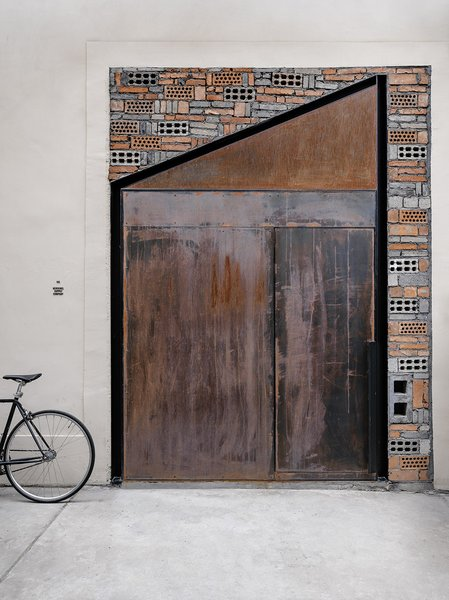 Reclaimed bricks and a pivoting, weathered steel door speak to the industrial flavor and salvaged materials found throughout this office renovation by architecture studio Linehouse. The result is a design that is both dramatic in form and texture, but subtle in its natural palette.