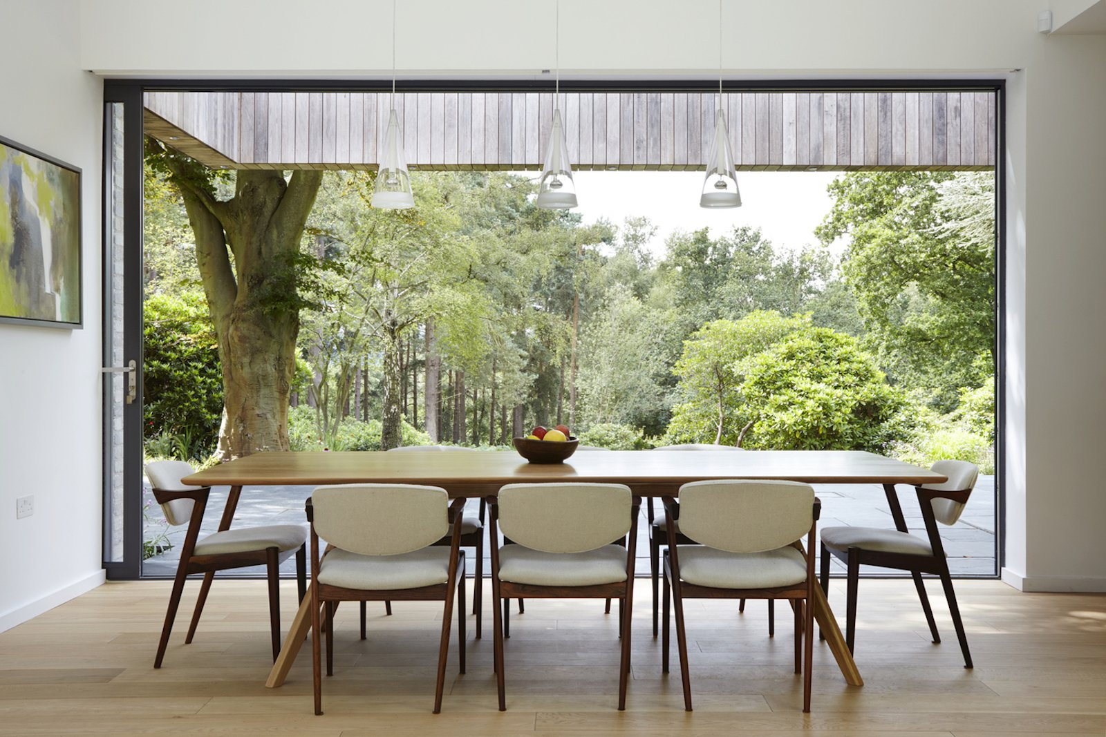 Dining Room, Table, Chair, Pendant Lighting, and Light Hardwood Floor London-based architecture and design studio Alma-nac designed House in the Woods, a contemporary home surrounded by pristine forest in England's South Downs National Park to replace a decrepit, 1950s bungalow. The new 240-square-meter dwelling retains the former building's simple gabled form and footprint, but offers greater flexibility with its ability to change from a single bedroom home to five bedrooms for large family gatherings.  Photo 6 of 10 in Raised in Just 10 Days, This Airtight Prefab Is a Lesson in Efficiency from 50 Modern Homes With Floor-to-Ceiling Windows