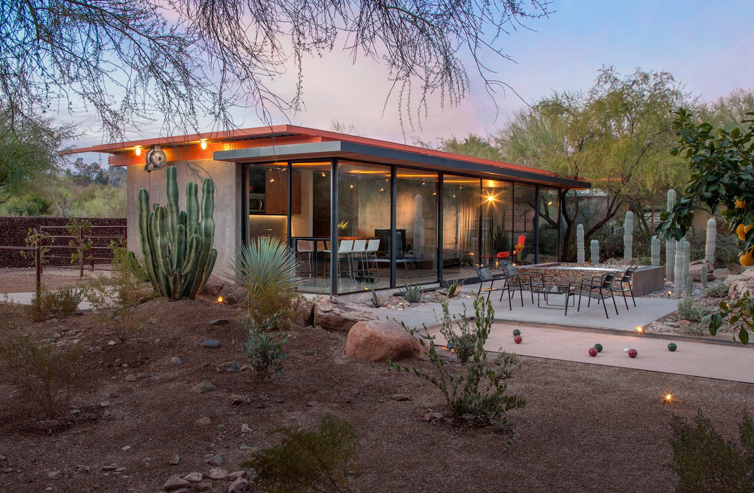 Outdoor, Desert, Hardscapes, Boulders, Trees, Concrete Fences, Wall, and Landscape Lighting Phoenix design-build firm The Construction Zone renovated an old concrete-and-steel barn, turning it into a sleek new guesthouse with an open-plan, three-room layout. Completed for approximately $300,000, the 790-square-foot adaptive reuse project carefully preserves the character of the existing structure while upgrading it to match the modern aesthetic of the main residence.  Photos from An Old Horse Barn Is Repurposed as a Chic Desert Guesthouse