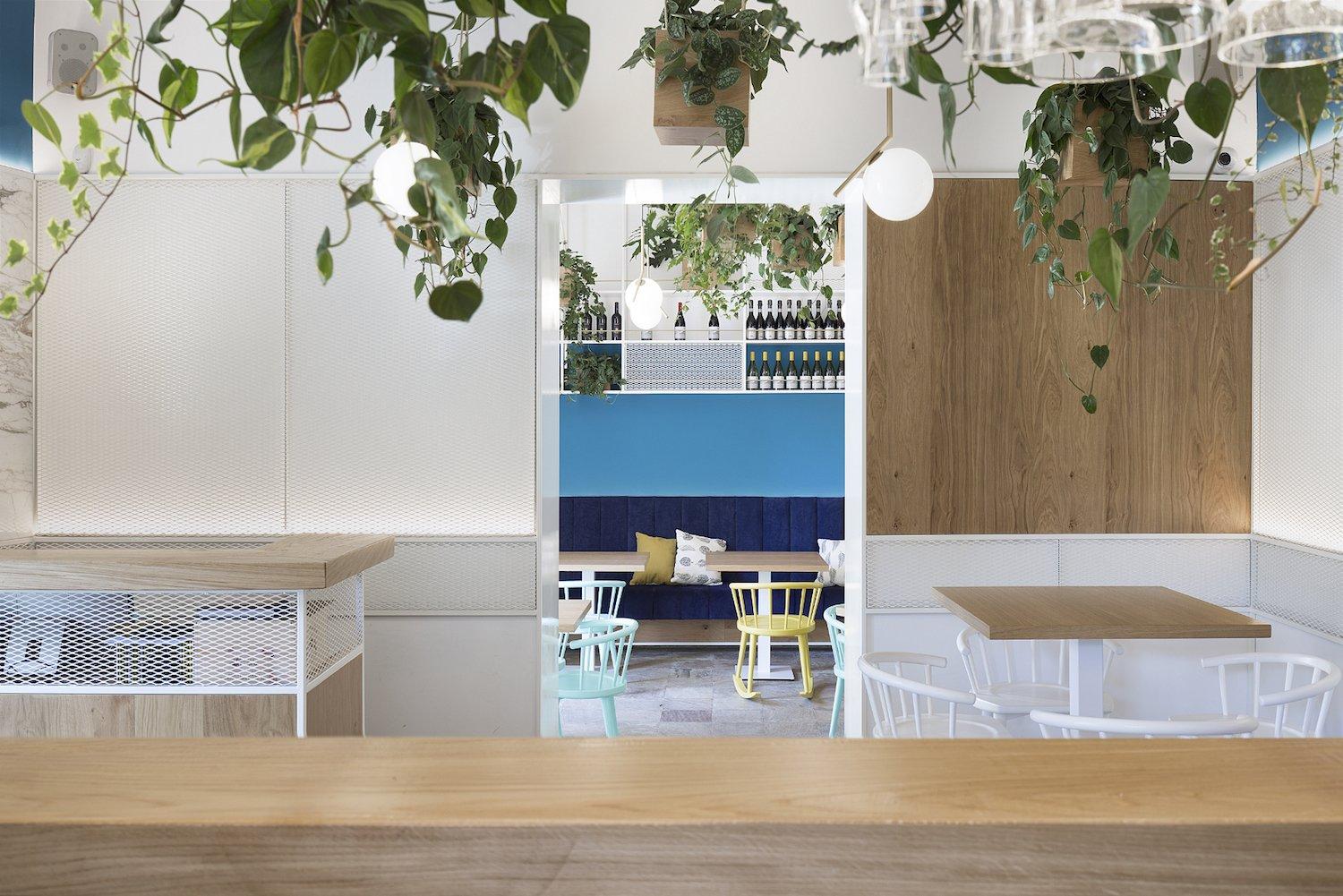 Dining Room, Chair, Pendant Lighting, Table, and Bench Materials in varying shades of blue bring the sky indoors.  Photo 7 of 10 in A Gloomy Basement is Reborn Into a Vibrant Italian Bistro