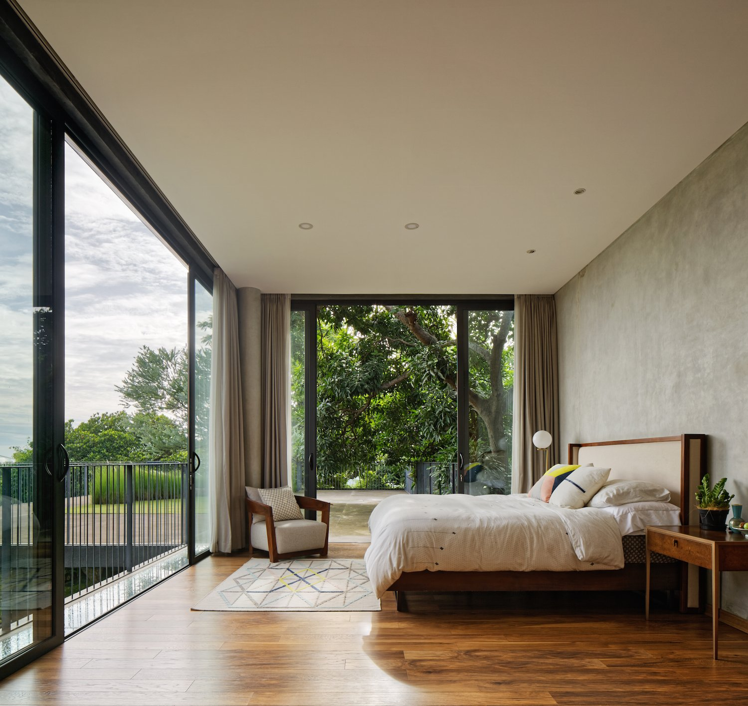 Bedroom, Bed, Chair, Recessed, Night Stands, Rug, Medium Hardwood, Floor, and Lamps The bedroom on the second floor has a treehouse-like feel.  Bedroom Medium Hardwood Floor Night Stands Rug Photos from This Concrete Abode Embraces Indonesia's Tropical Climate