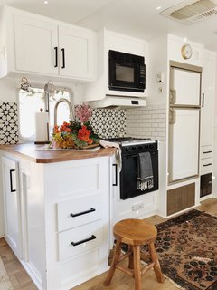 The compact kitchen features a ceramic tile backsplash.