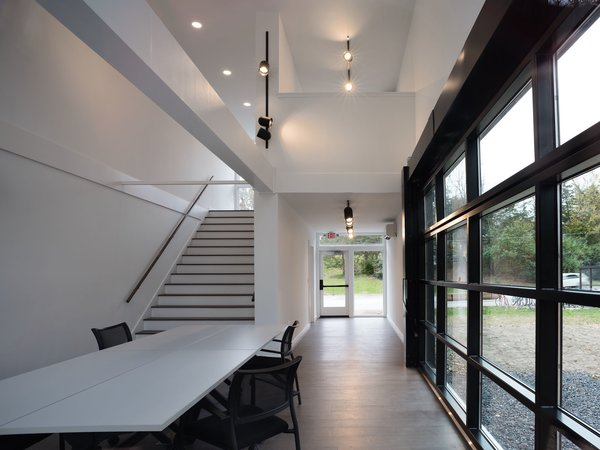 Stairs lead up to a small loft-like office that overlooks the meeting room below.