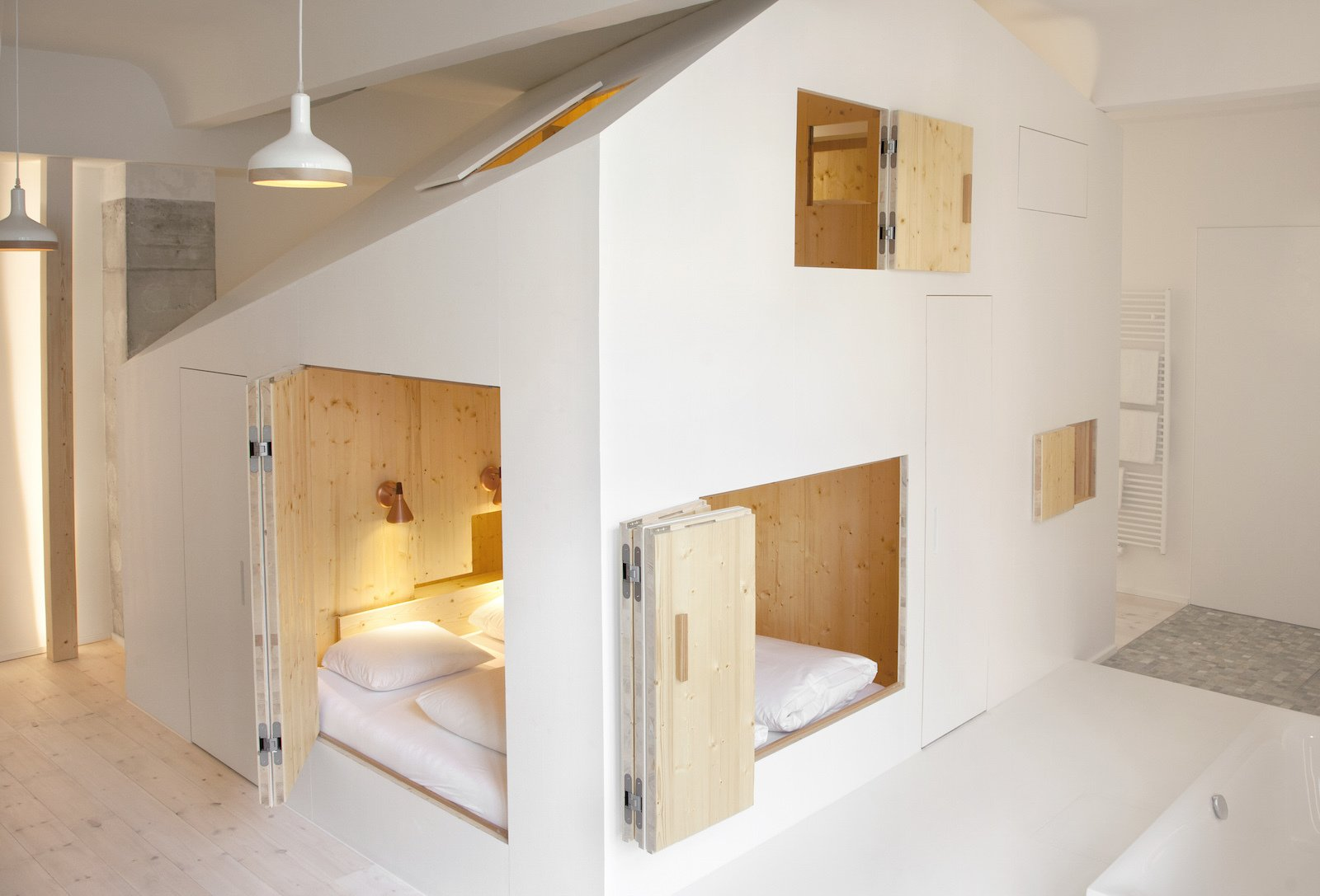 Bedroom, Pendant Lighting, Bed, Wall Lighting, and Light Hardwood Floor Following the house-within-a-house concept, this playful playhouse-like addition features an all-plywood interior.  Photos from Stoke Your Imagination With This Playhouse-Like Suite in Berlin