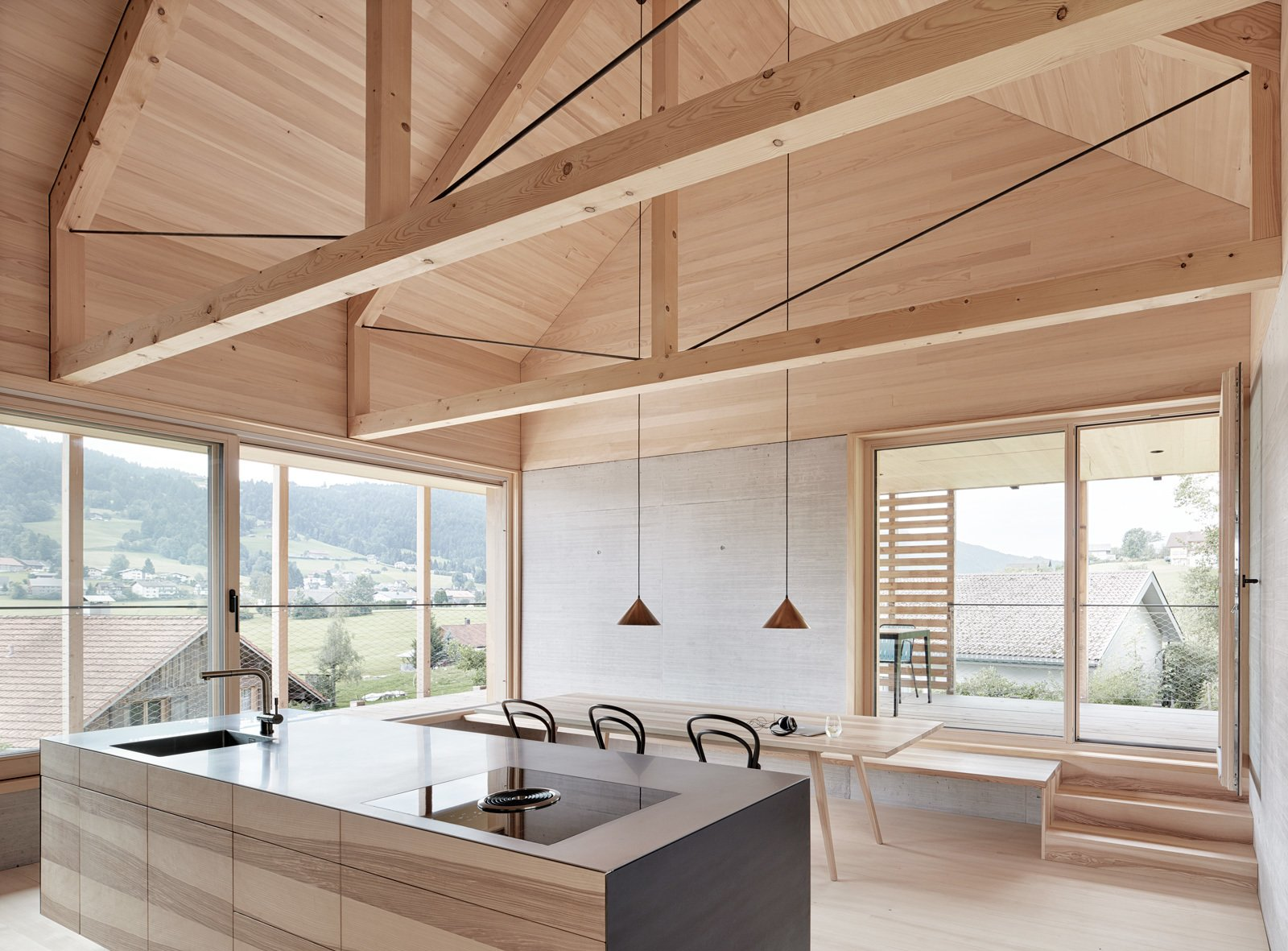 Dining, Pendant, Chair, Table, Bench, and Light Hardwood Exposed trusses celebrate the home's timber construction.  Best Dining Light Hardwood Chair Bench Photos from A Minimalist Home Is Built Into Steep Terrain in an Austrian Valley