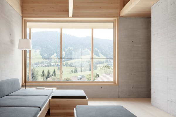 Large windows frame views of the rural Austrian valley.