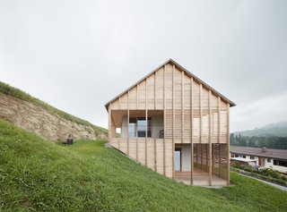 The gabled roof ridge of Höller House by Innauer-Matt Architekten is parallel to the hill.