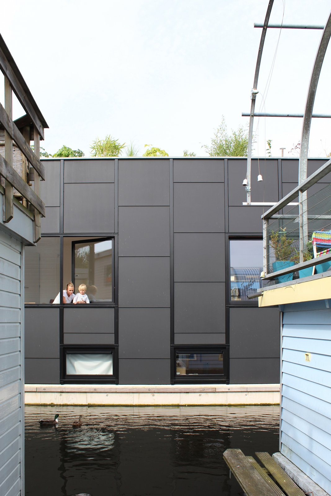Exterior, Metal Siding Material, Boathouse Building Type, and Flat RoofLine Ducks swim close to the windows.  Best Photos from An Architect Creates a Two-Level Houseboat For His Family on a Tight Budget