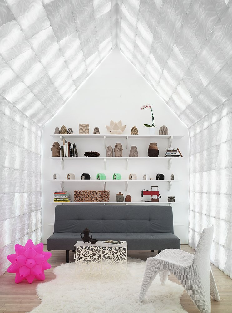 Living Room, Sofa, Coffee Tables, Chair, Shelves, Light Hardwood Floor, Rug Floor, and Floor Lighting The home is an experiment in livable and attractive 3D printed architecture.  Photo 4 of 12 in This 3D-Printed Tiny Cabin Offers a Creative Response to the Bay Area's Housing Crisis