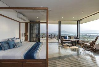 The master bedroom opens up to a small terrace through full-height glazed sliding doors.