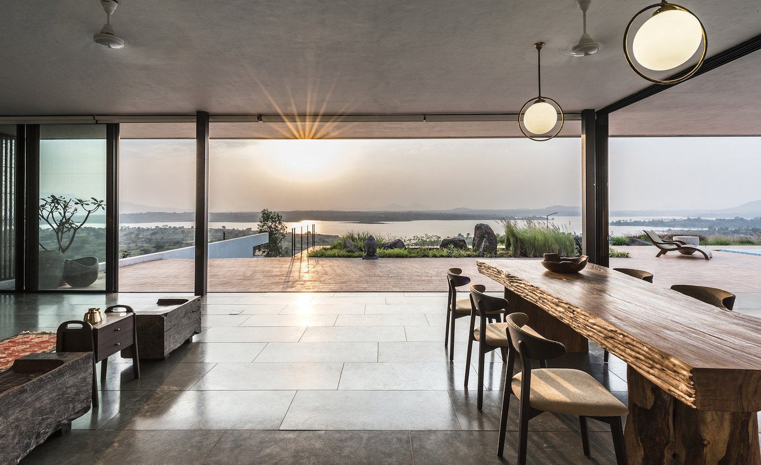 Dining Room, Table, Chair, and Pendant Lighting The open-plan dining and living area flow seamlessly into the outdoor terracotta terrace.  Photo 7 of 14 in A Modern Home in India Evokes Emotion With a Giant 4-Ton Rock