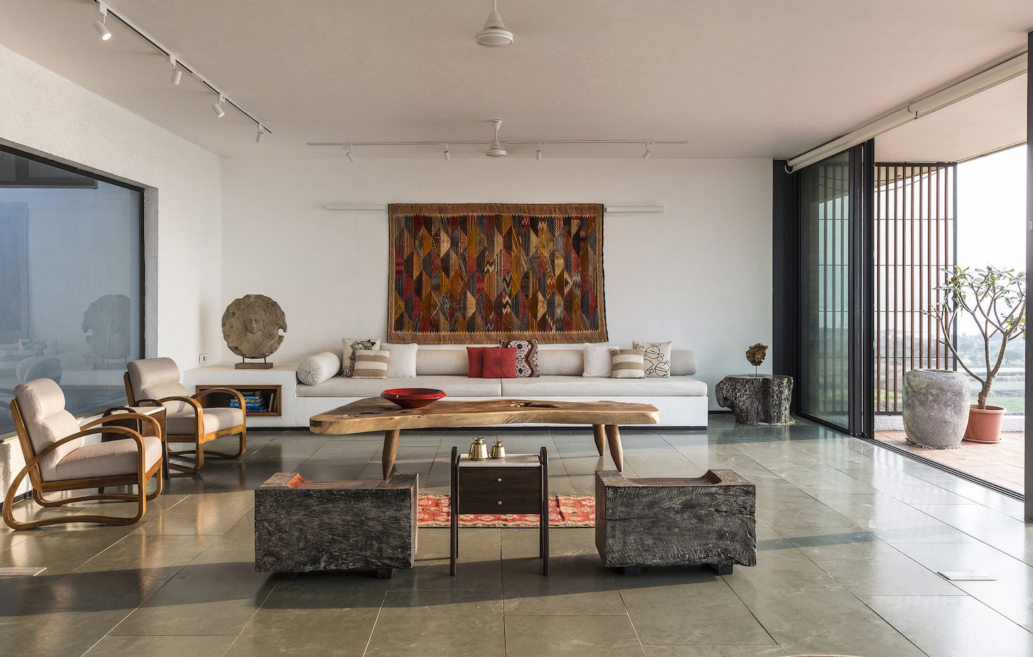 Living Room, Track Lighting, Pendant Lighting, Coffee Tables, Sofa, Chair, End Tables, and Rug Floor A tree-stump end table adds a dose of organic style to the modern living area.    Photo 6 of 14 in A Modern Home in India Evokes Emotion With a Giant 4-Ton Rock